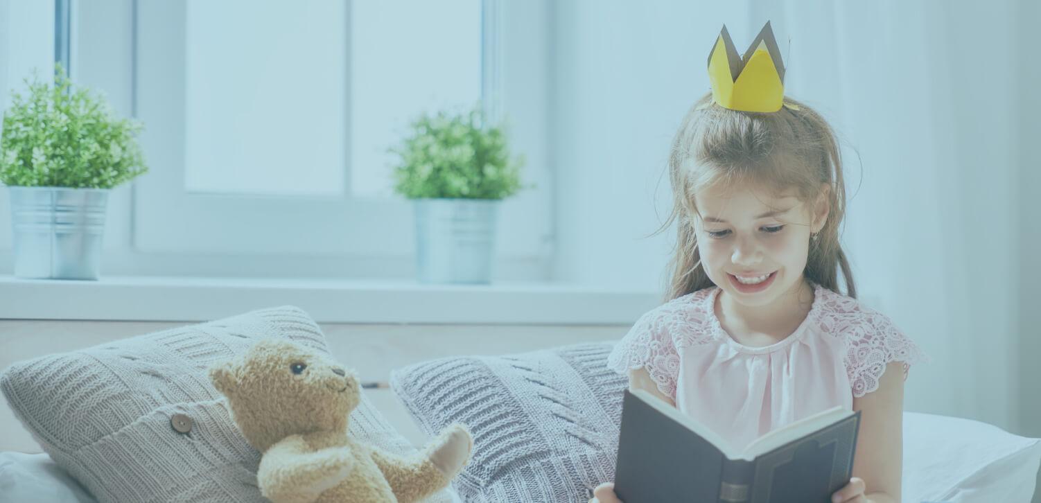 Girl reading book to teddy bear