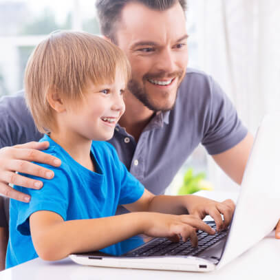 Dad helping son on computer