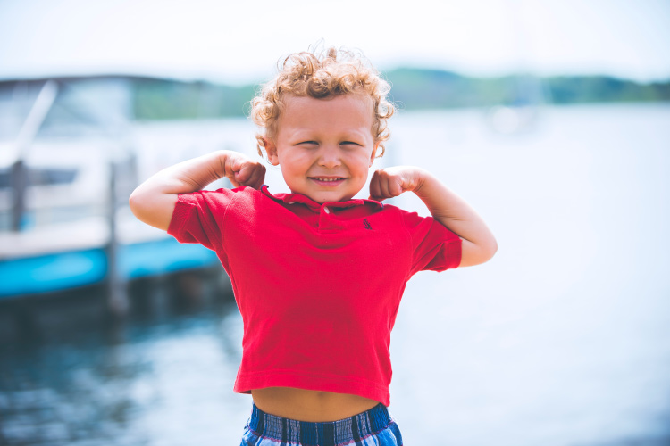 Young boy wearing a red polo flexes his arms saying kids are strong and able to combat their dental fear