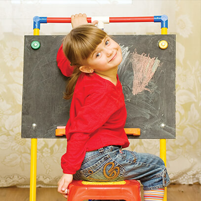 Young girl coloring on a chalk board