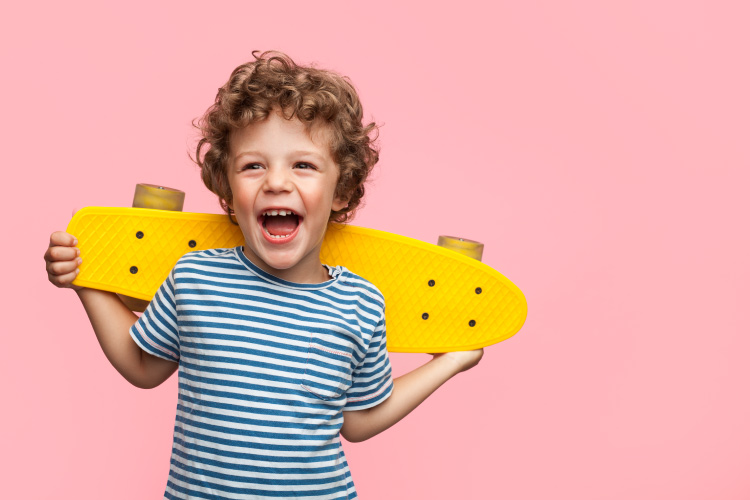 Curly-haired little boy holds a yellow skateboard and smiles against a pink wall