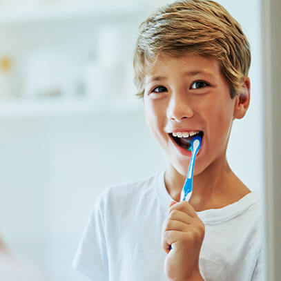 Happy boy brushing his teeth