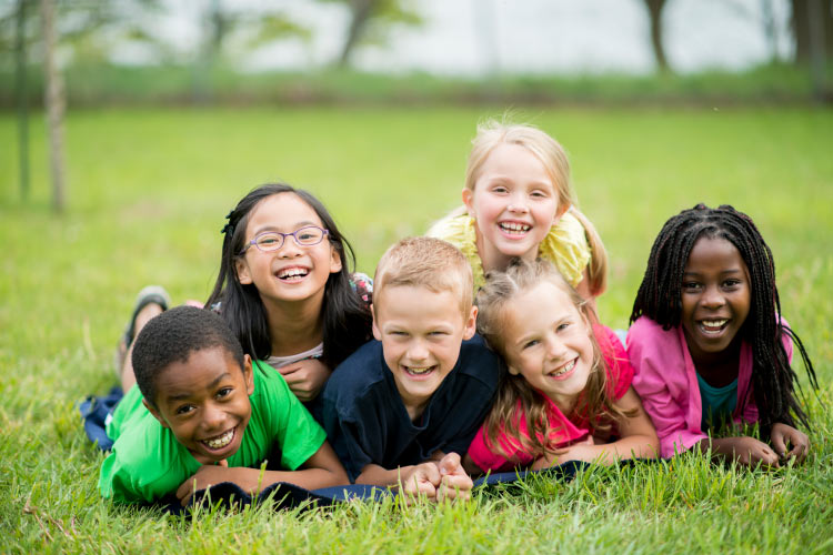 Group of multiracial kids smile without cavities in the grass by Storybook Smiles in Tyler, TX