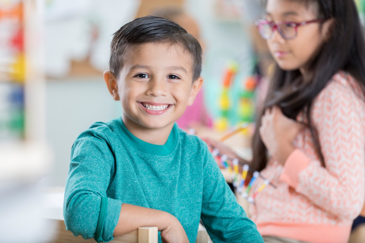Dark-haired boy in teal shirt smiles with strong teeth fortified with fluoride in Tyler, TX