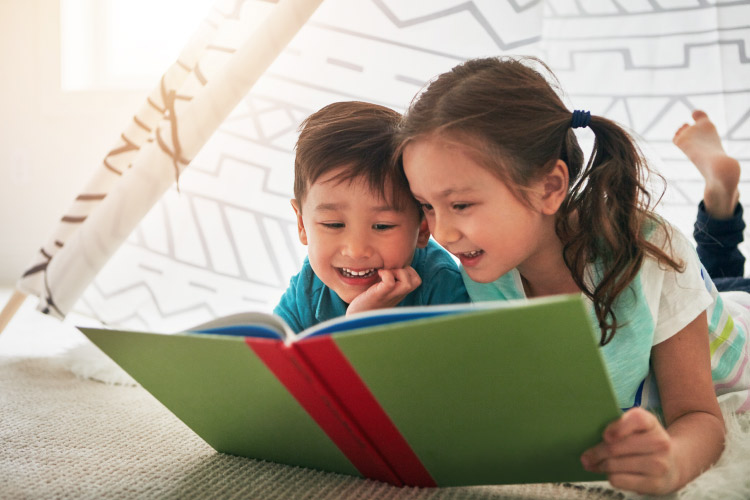 A brother and sister smile as they read a children's book about the dentist
