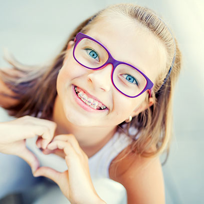Girl with glasses and braces smiling