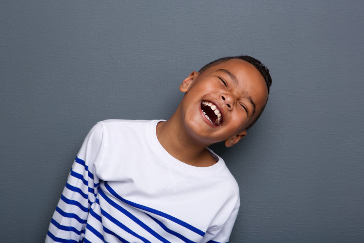 Dark-haired boy in a white and navy striped shirt smiles against a gray wall after visiting a children's dentist