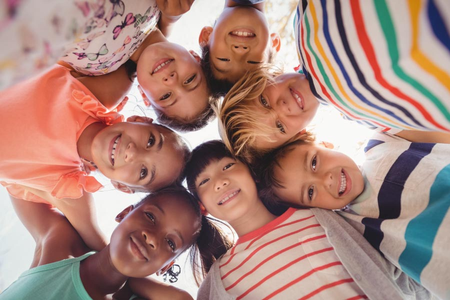Looking up into the faces of a group of children huddled together after visiting their pediatric dentist