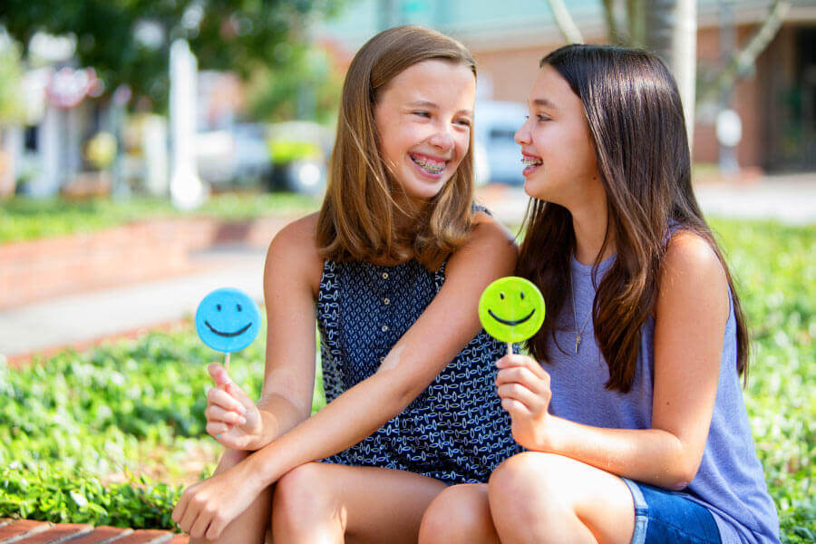 Two girls wear braces and smile at each other while sitting down with sugar-free lollipops in Tyler, TX
