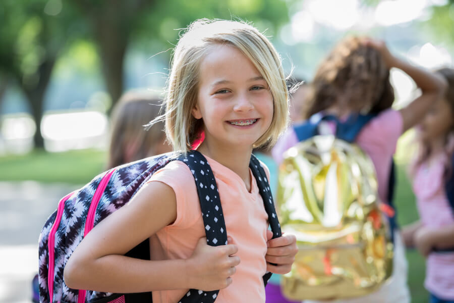 Blonde girl wears braces as she carries her backpack into school