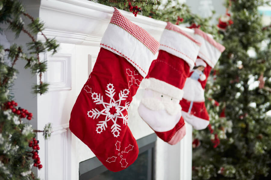 Closeup of red stockings hanging on the fireplace mantle waiting for Christmas stocking stuffers for kids