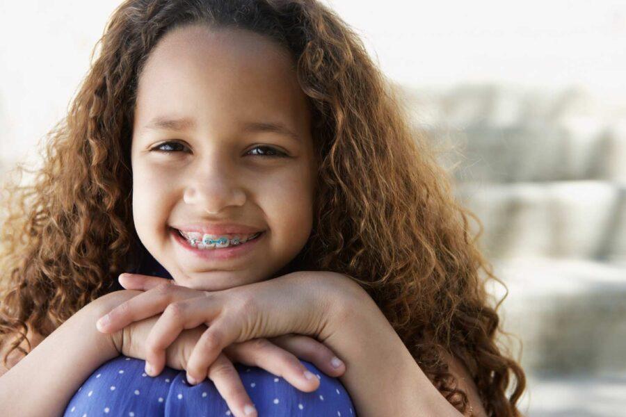 Brunette girl with interceptive orthodontics smiles with her hands on her knees outside her pediatric dentist in Tyler, TX